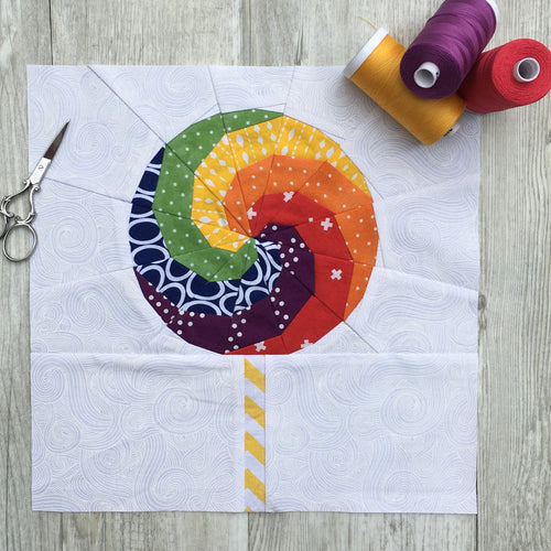 Swirly Lollipop FPP Block Pattern by Penny Spool Quilts. Foundation paper pieced quilt block pattern, sample is shown in rainbow colours wih yellow and white striped stick, on white background. Shown with spools of thread and small scissors.