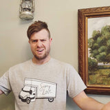 Sorry love grey t-shirt as worn by a male model by a wall adorned by a lamp and a painted scenic art piece, the print features a luton van with the words sorry love scrawled on the side.