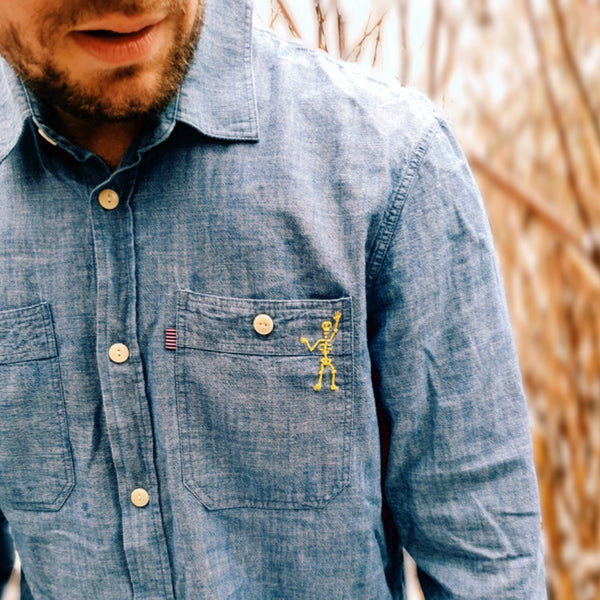 A close up of the skelebob long sleeve denim shirt. showing the embroidered yellow skeleton that has been hand sen onto the pocket.