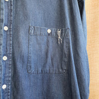 close up of the denim shirt, with skeleton embroidered in white thread.