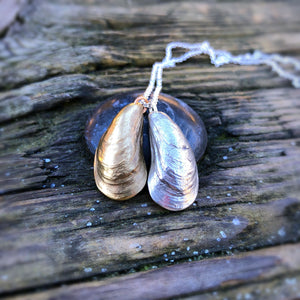 pendant comprised of two mussel shells with incredible detail that have been cast in metal: one in sterling silver the other golden. on white background.