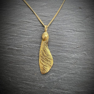 "solo maple key necklace  ""helicopter"" in golden on a slate background"