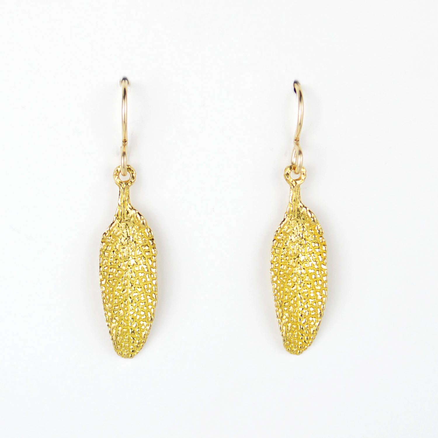 golden sage leaf earrings on plain white background. incredible detail