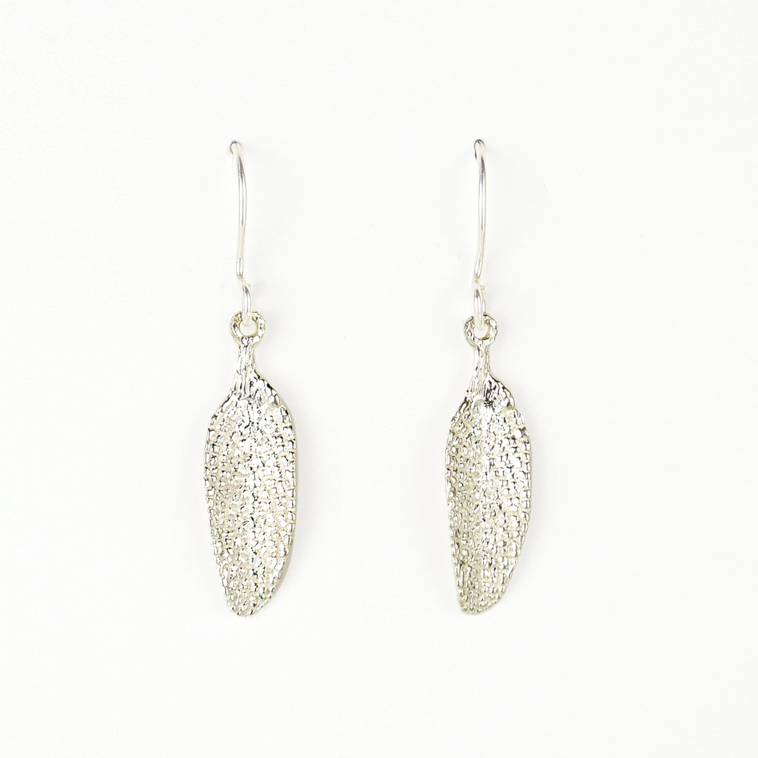 silver sage leaf earrings on plain white background. incredible detail