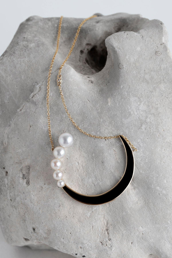Louella - NAiiA - 14K solid gold freshwater pearl and black enamel crescent moon necklace with one diamond on gold chain on rock