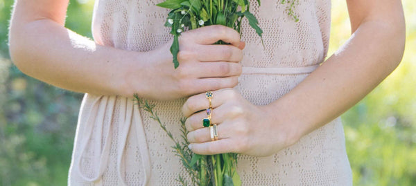 girl holding fowers in a field jewelry by hot crown