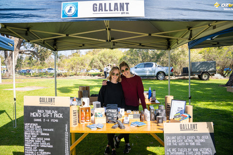 two girls standing behind a men's gift shop market stall table