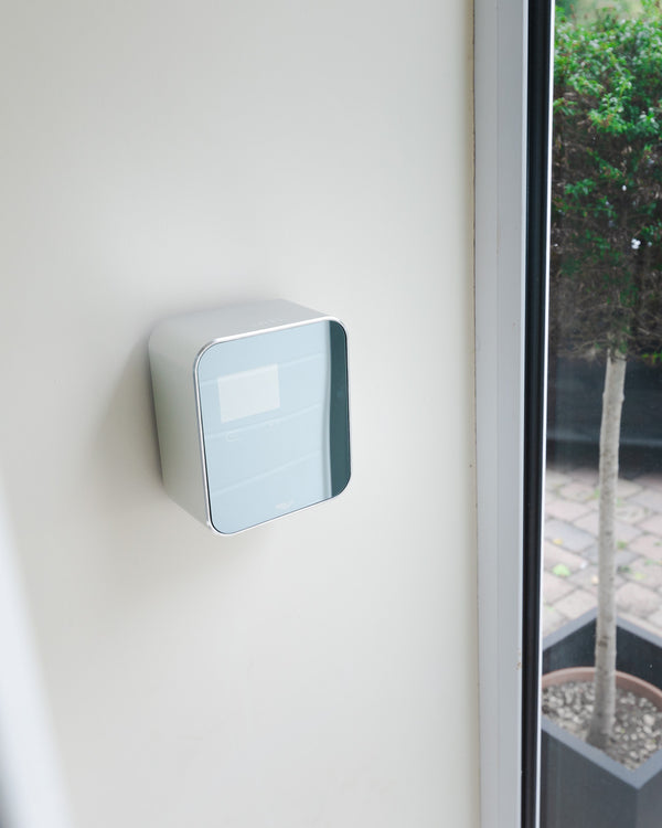 silver, square, automatic hand sanitiser and soap dispenser wall mounted by a front door