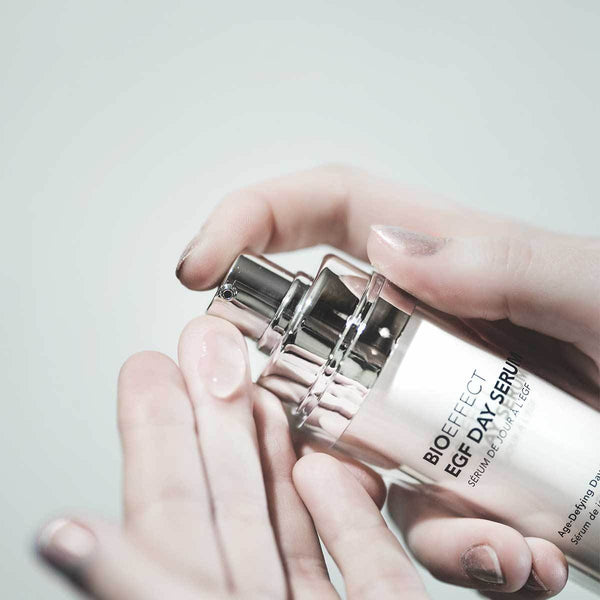 Woman's hands holding a bottle of BIOEFFECT EGF Day Age-Defying Serum with a silver lid and squeezing a small amount onto her left hand. Her nails are painted with a light silver glitter.