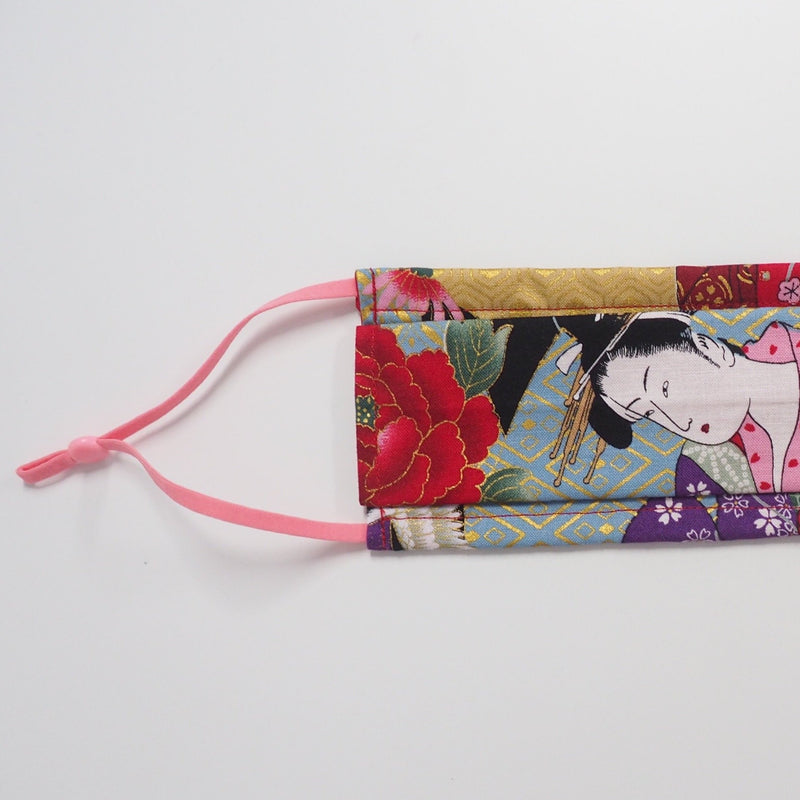 Rectangular two-fold barrier face mask with a Japanese geisha print and pink adjutsable elastics laid flat on a white background