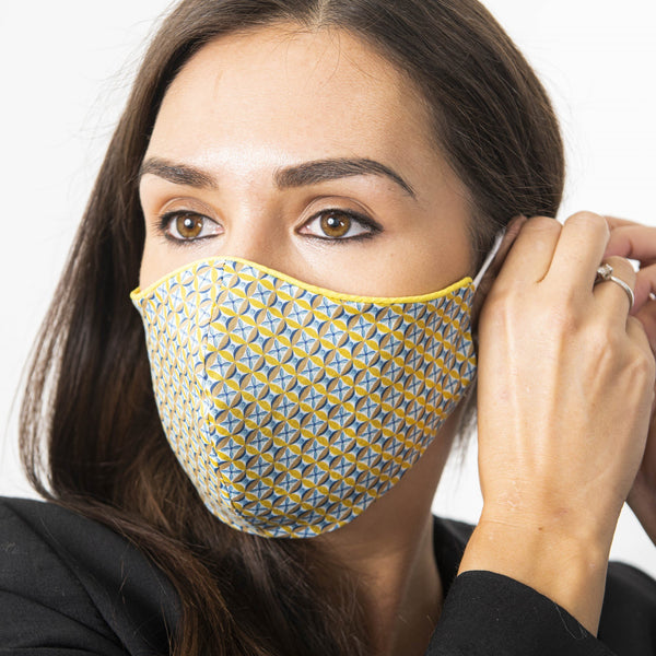 Female model adjusting a blue and mustard Liberty London print face mask. The face mask has yellow piping.