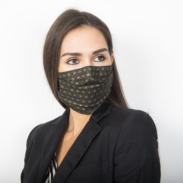 Female model wearing a black fabric face mask with a metallic golden Japanese geometric star print.