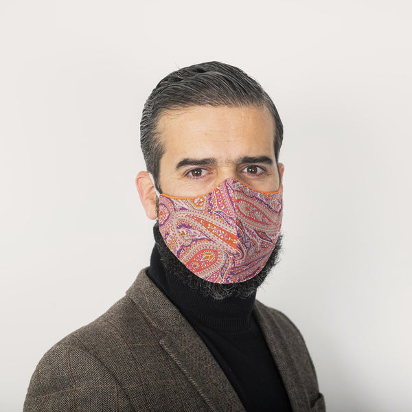 Male model wearing a sleek-fitting pink Liberty London paisley print face mask securely over his beard. The mask has orange Tana Lawn piping.