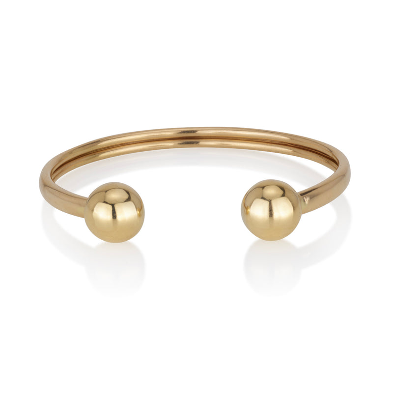 An open bracelet with two solid gold balls