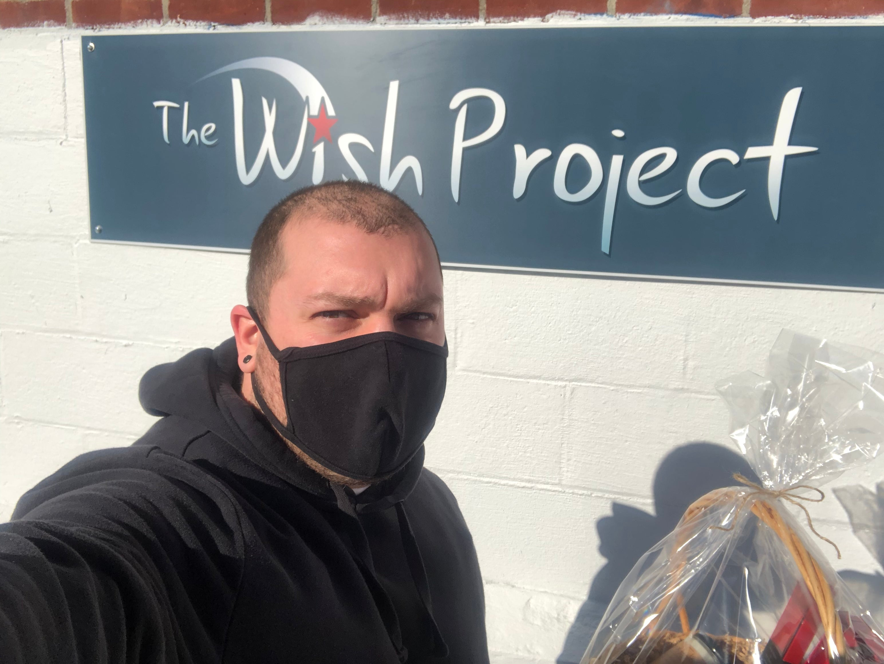 Fern x Flow owner, Joe Wing, in front of The Wish Project's sign outside their Chelmsford, MA location.