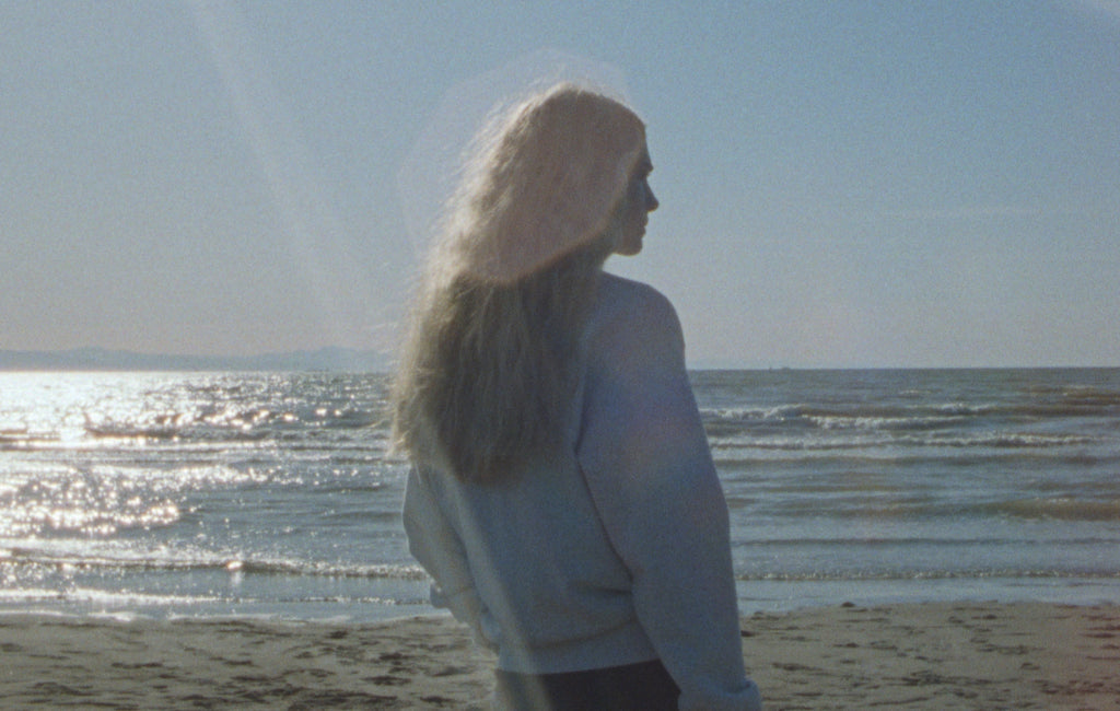 Body of Work - Return to Nature - Image of a woman in a grey sweatshirt facing the ocean.