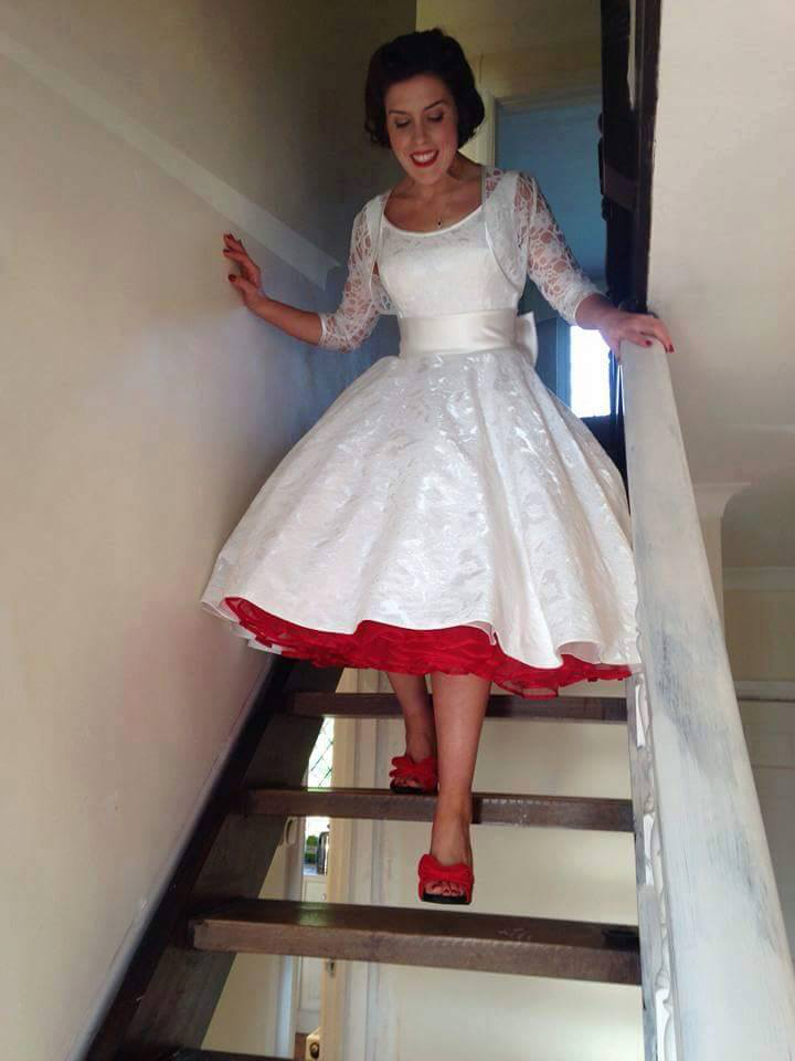 da9a3839bdb0 This bride added fabulous red shoes and red petticoat to her tea length  ivory brocade wedding gown. The pop of red adds to the vintage ...