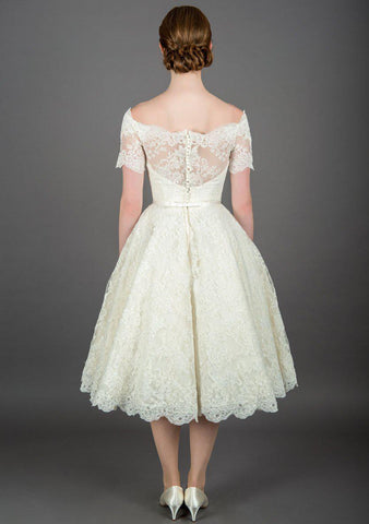 Rear view of Nina tea length vintage inspired lace dress with off the shoulder neckline and trimmed with a satin bow belt