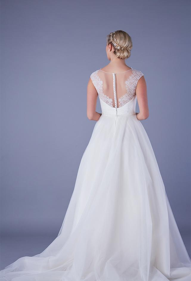 Back of Tea length wedding dress with plunge lace illusion bodice and tulle skirt with pearl and bead waist detailing.
