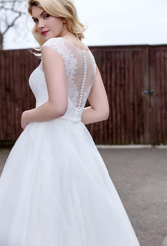 Close up of back of Tea length wedding dress with plunge lace illusion bodice and tulle skirt with pearl and bead waist detailing.