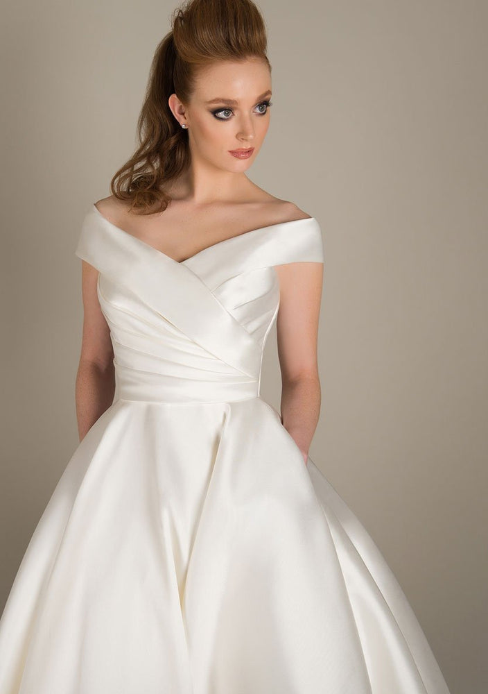 Deluxe Mikado wedding gown with dress with beautifully pleated bodice, wide neck line and full Mikado skirt with pockets completes this classic gown. Just beautiful!  Also available in shorter tea and Fifties lengths.
