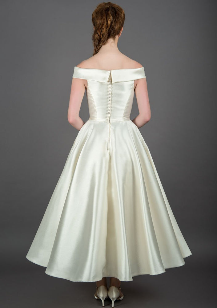 Back of 50's length off the shoulder dress, with full circle skirt and pockets, trimmed with a satin bow belt
