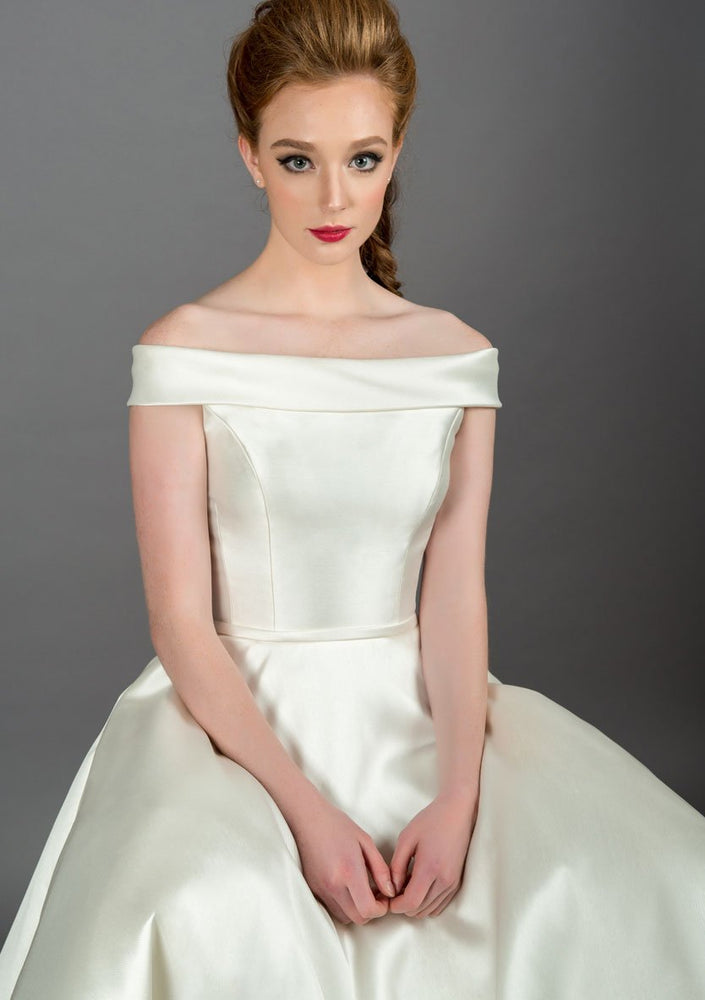 Closeup of 50's length off the shoulder dress, with full circle skirt and pockets, trimmed with a satin bow belt