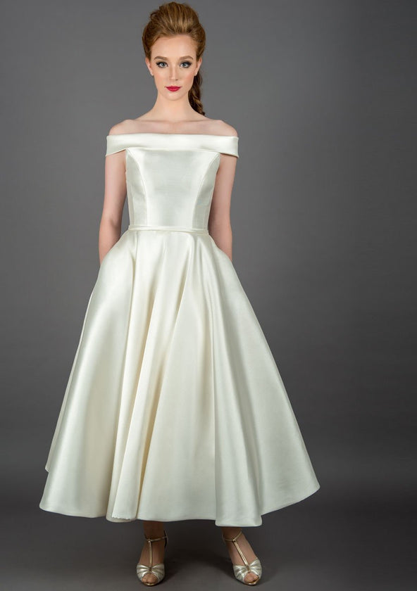 50's length off the shoulder dress, with full circle skirt and pockets, trimmed with a satin bow belt