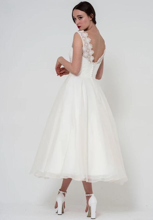 Image of back of dainty floral lace bodice with floaty organza tea length skirt wedding gown by Freda Bennet