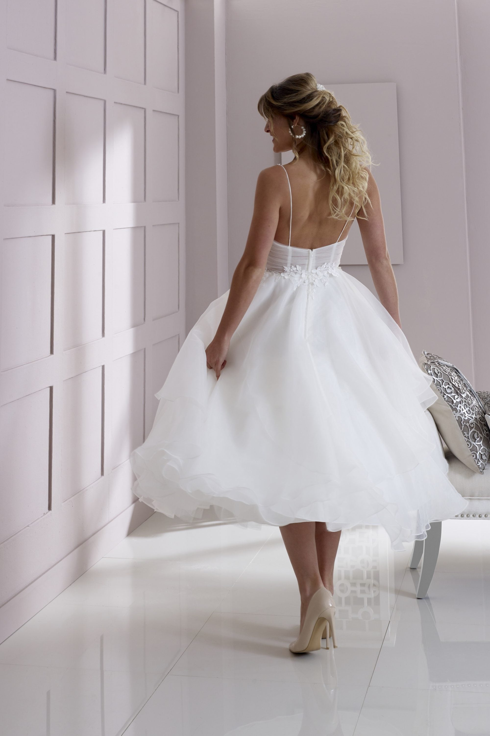 Back of organza and lace appliqué tea length wedding gown with tiered skirt and luxury floral petal details.