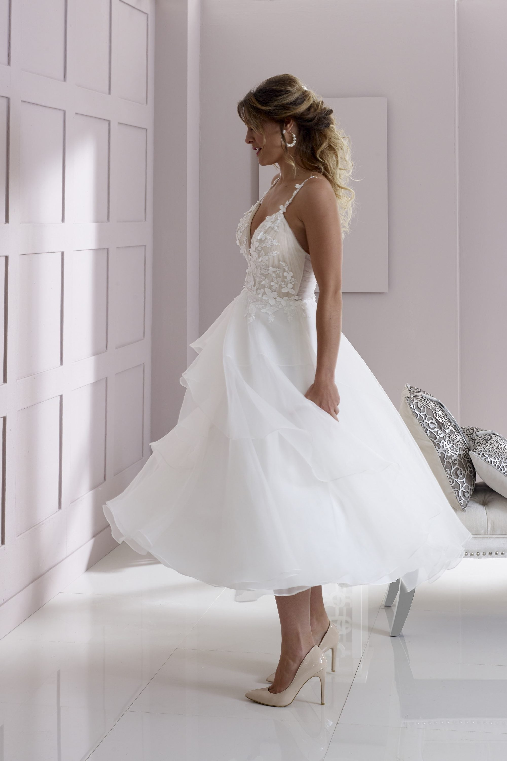 Organza and lace appliqué tea length wedding gown with tiered skirt and luxury floral petal details.