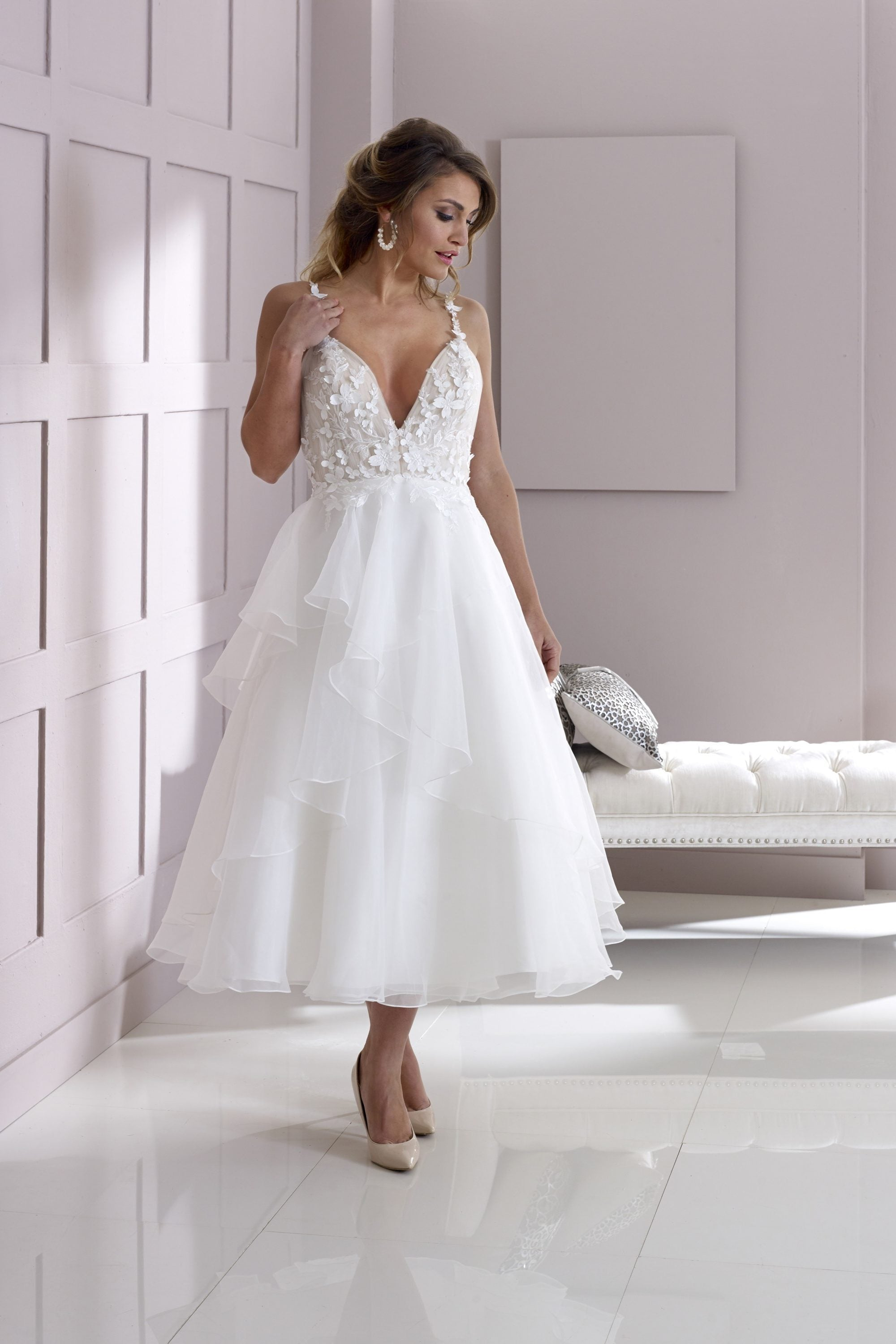 Organza and lace appliqué tea length bridal gown with tiered skirt and luxury floral petal details.