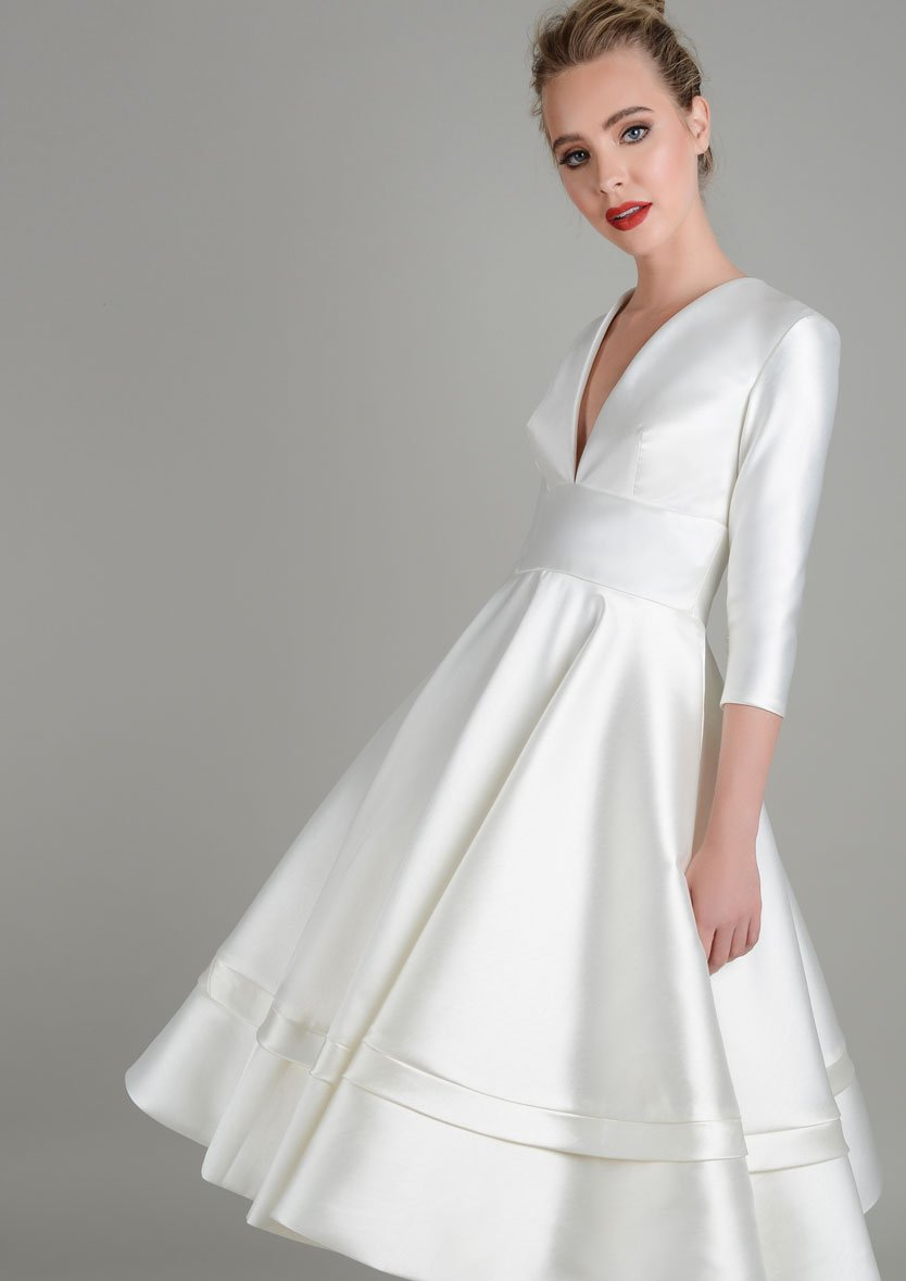 Close up of tea length wedding gown featuring full sleeves and deep v neck bodice.