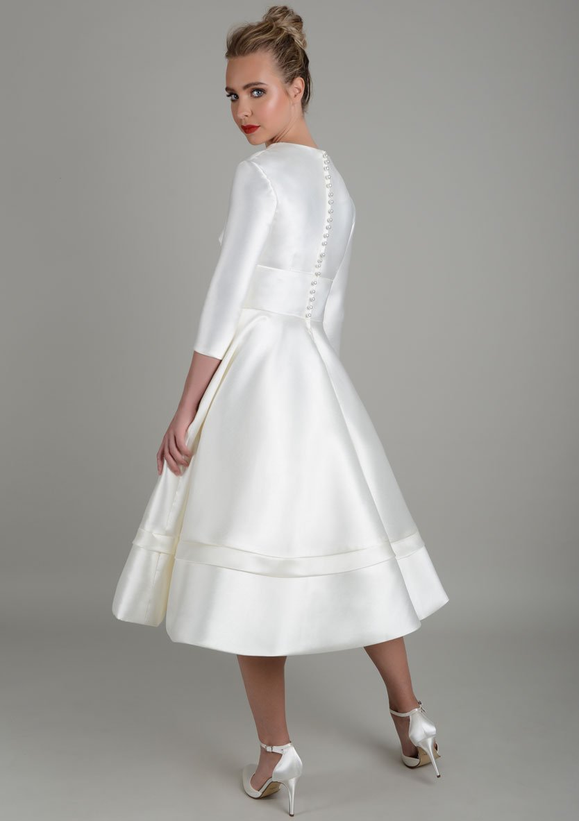 Back of tea length wedding gown featuring full sleeves and deep v neck bodice.