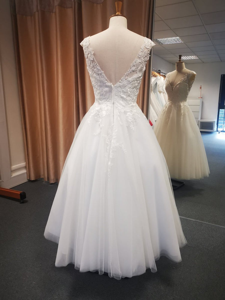 Back of lace bodice wedding dress featuring V back and full tea length tulle skirt.