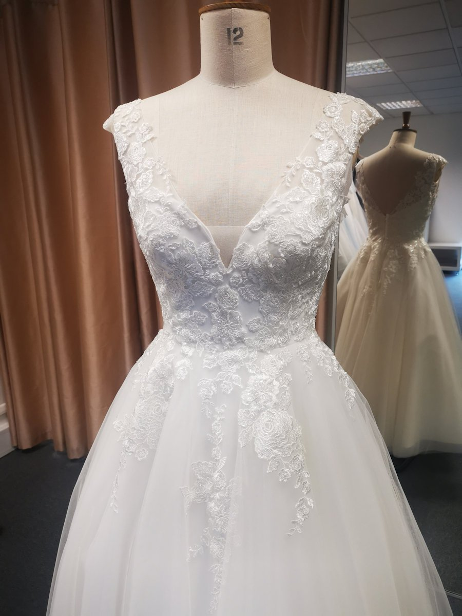 Bodice of lace bodice wedding dress featuring V back and full tea length tulle skirt.