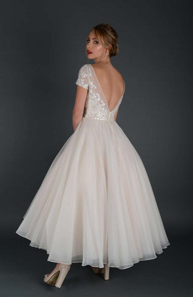 Back of tea length bridal gown with embellished bodice and cap sleeve.