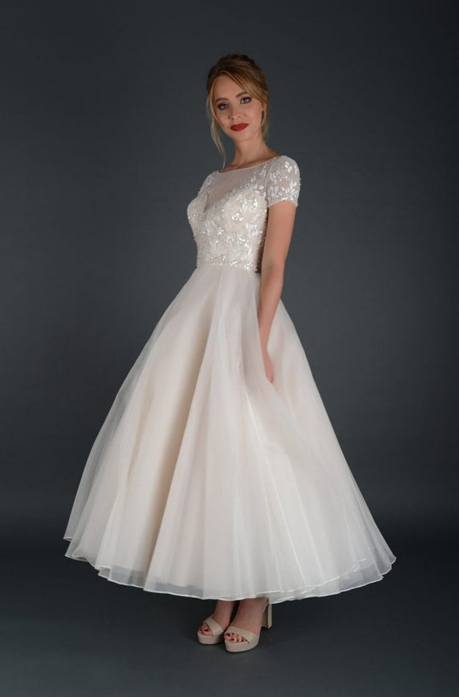 Side of tea length bridal gown with embellished bodice and cap sleeve.
