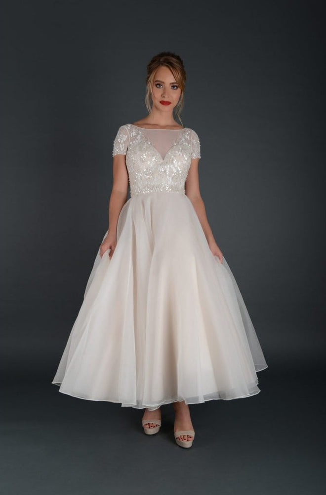 Tea length bridal gown with embellished bodice and cap sleeve.