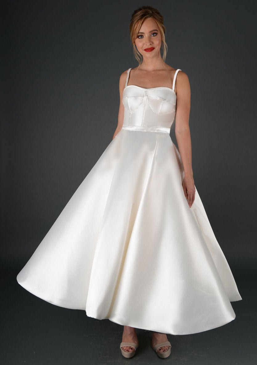 Image of Strapless satin fashion forward bridal gown with thin straps, neat fitted waist and full skirt.