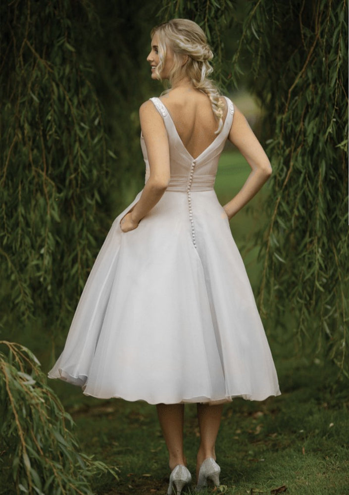 Back of vintage inspired  short 40's style wedding gown with fine appliqués to the shoulders, pleated fitted bodice and full fifties organza skirt