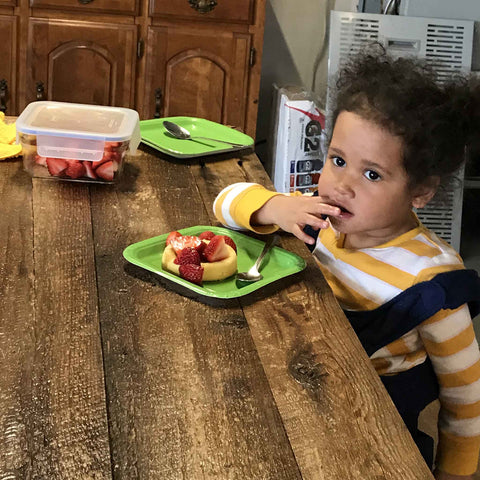 Young boy eating strawberry shortcake with maple syrup
