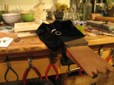 Jewellery workbench with tools, bench peg, a selection of pliers and some white gold wedding ring bands,