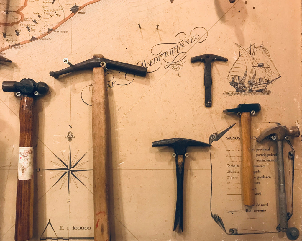 Selection of jewellery hammers and tools hanging against a backdrop of an old map of the Mediterranean Sea and Coast
