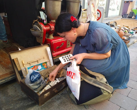 Search for special old buttons and other curious trinkets in an antique market.