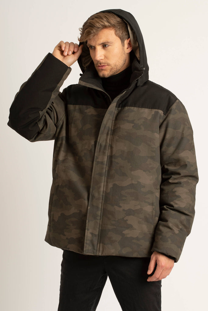 Man wearing a zipped up Tough Duck Black Gadwall Hip-Length Parka in Camo and Black with the hood up.
