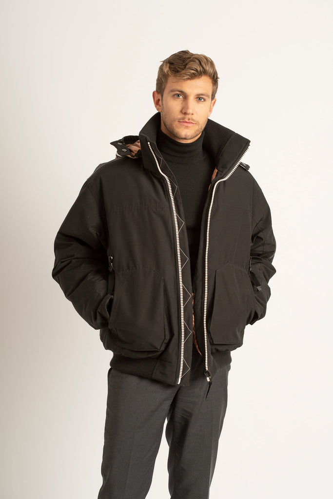 Man wearing a Tough Duck Black Widgeon Bomber in black that's unzipped.