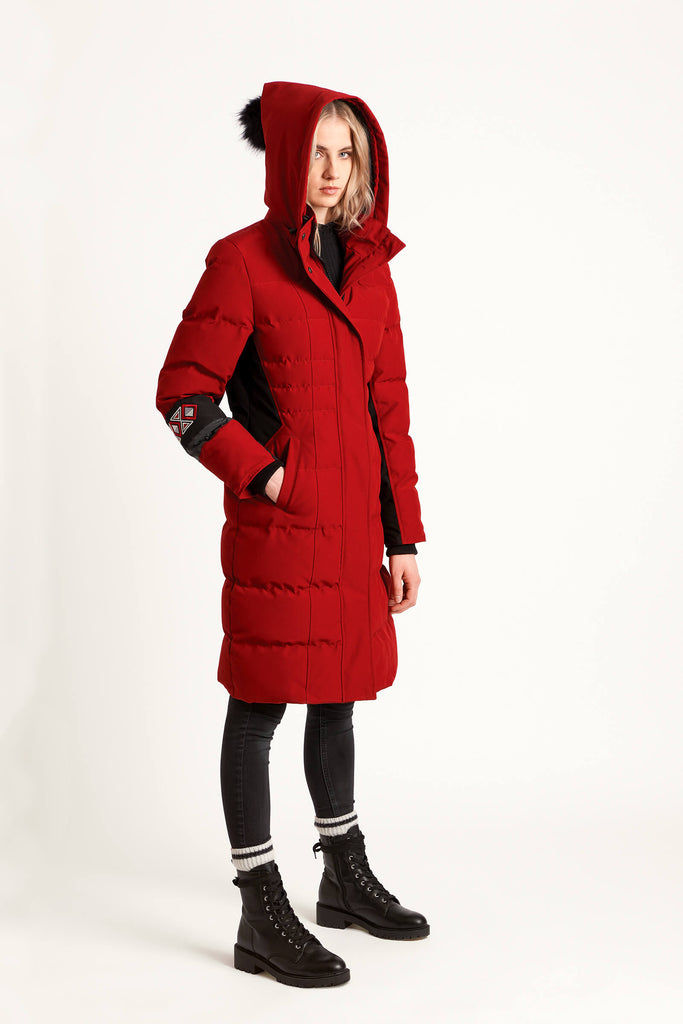 Women wearing a Tough Duck Black Merganser Calf-Length Jacket in red and black with the hood up.