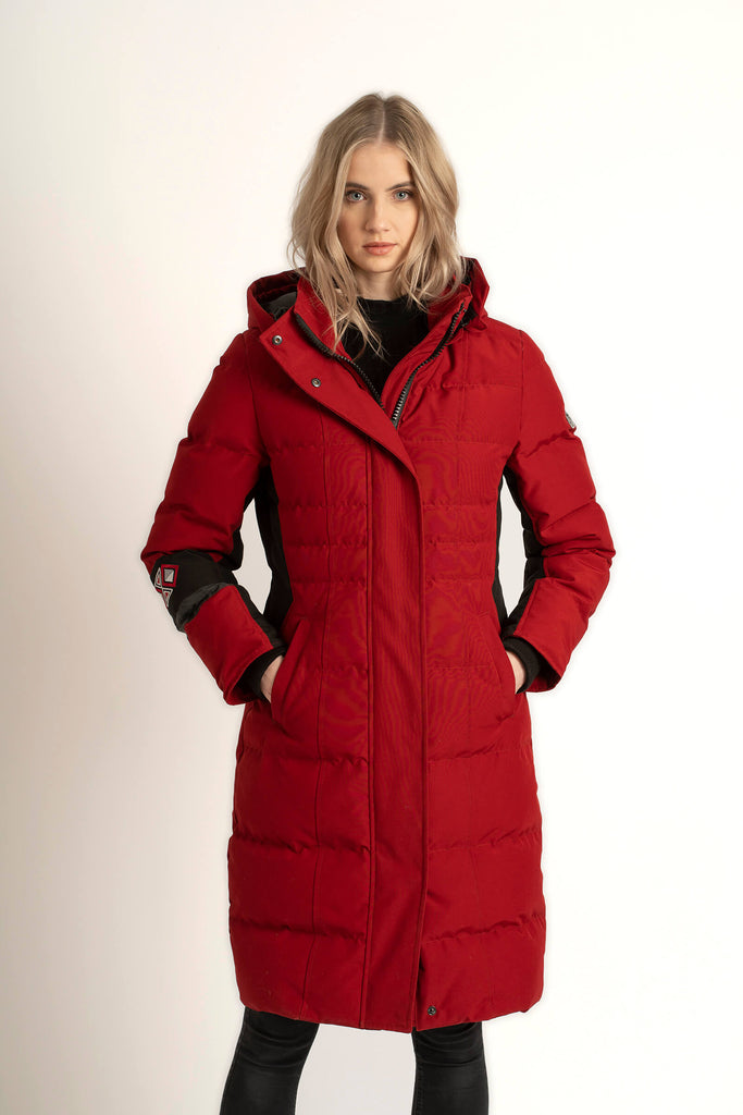 Women wearing a Tough Duck Black Merganser Calf-Length Jacket in red and black with her hands in her pockets.