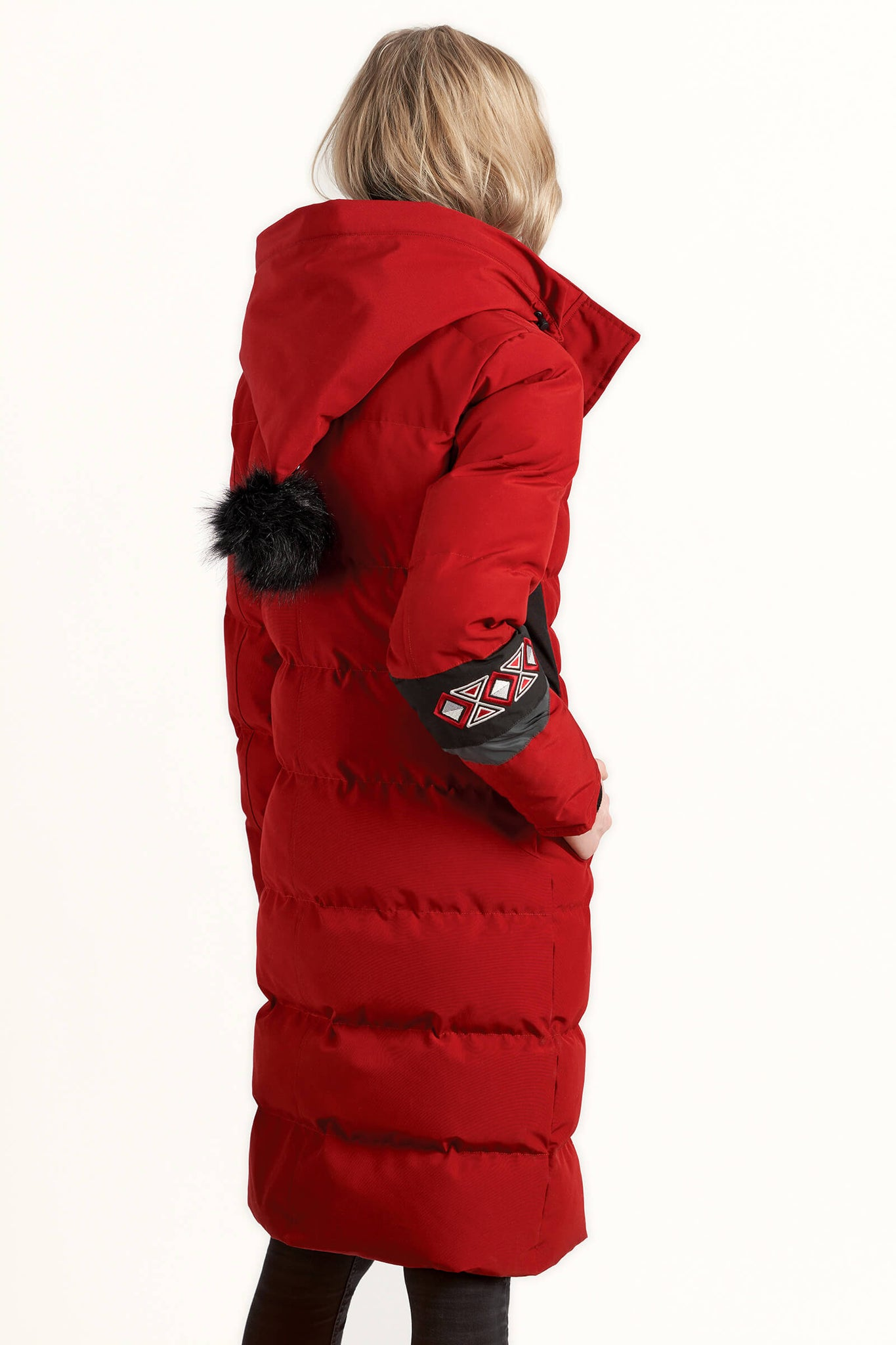 The back view of a women wearing a Tough Duck Black Merganser Calf-Length Jacket in red and black while looking into the distance.